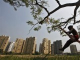 a-boy-plays-on-a-swing-suspended-from-a-tree-in-front-of-a-residential-estate-under-construction-in-kolkata-2-2