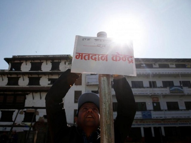 "An election officer sets up a sign that reads ""polling station"" a day ahead of the parliamentary and provincial elections in Kathmandu, Nepal December 6, 2017.  PHOTO: REUTERS"