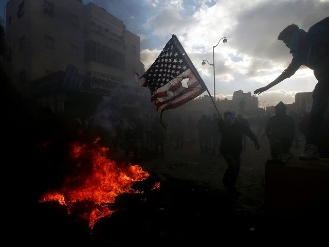 A Palestinian protester prepares to burn a US flag during clashes with Israeli troops near the Jewish settlement of Beit El, near the West Bank city of Ramallah December 7, 2017. PHOTO: REUTERS