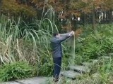The video shows the man turning the cloth over as he stands in the middle of a bush. He opens the cloth and disappears in front of the camera. YOUTUBE SCREEN GRAB