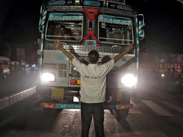 A member of the Bhartiya Gau Raksha Dal cow vigilante group raises his arms to stop a truck at a roadblock set up in the northern Indian city of Chandigarh in early July.  PHOTO: REUTERS