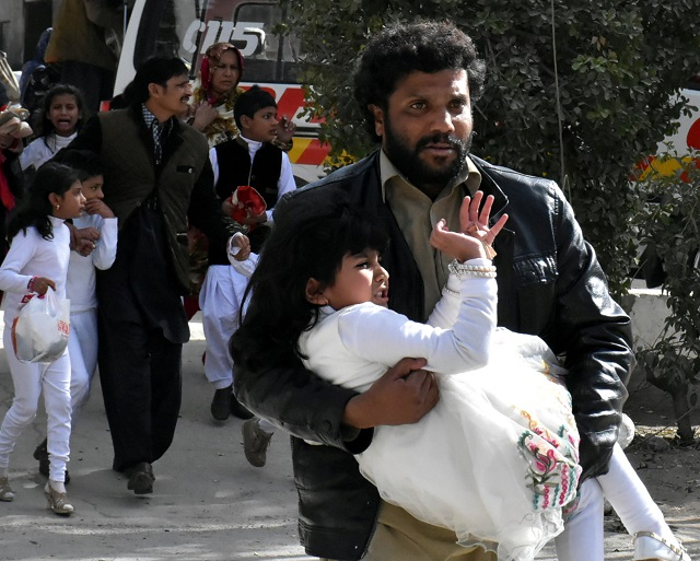 A man carries a girl as he runs out with others after gunmen attacked the Bethel Memorial Methodist Church in Quetta, December 17, 2017.  PHOTO: REUTERS
