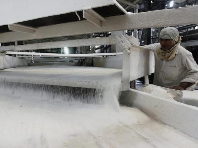 A worker checks the flow of sugar inside a sugar factory. PHOTO: REUTERS