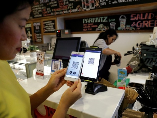 Frances Sy pays for her coffee with cryptocurrency at the opening of Ducatus cafe, the first cashless cafe that accepts cryptocurrencies such as Bitcoin, in Singapore December 21, 2017.  PHOTO: REUTERS