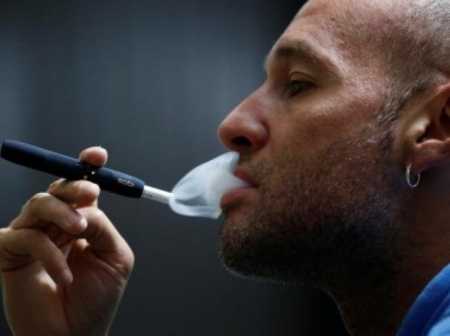 A man poses for a photograph while using a Philip Morris iQOS smoking device. PHOTO:REUTERS.