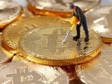 a-small-toy-figure-is-seen-on-representations-of-the-bitcoin-virtual-currency-in-this-illustration-picture