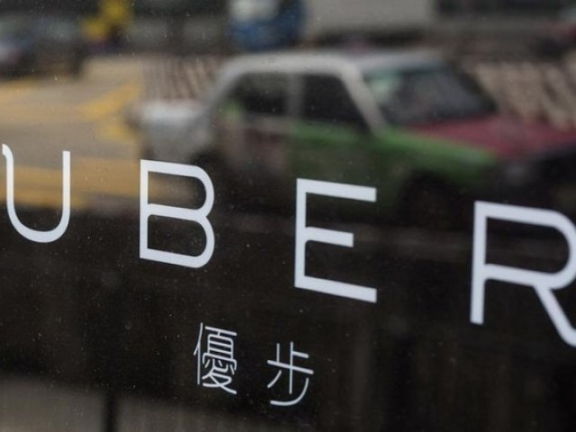 A taxi is reflected in a window at the office of taxi-hailing service Uber Inc in Hong Kong China