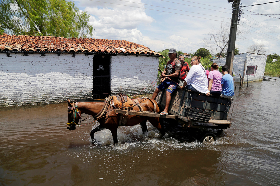 People ride on a horse carriage through a flooded street after heavy rains caused the river Paraguay to overflow, in Asuncion, Paraguay. PHOTO: REUTERS