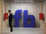 a-man-waits-for-an-elevator-in-front-of-a-logo-at-facebooks-headquarters-in-london