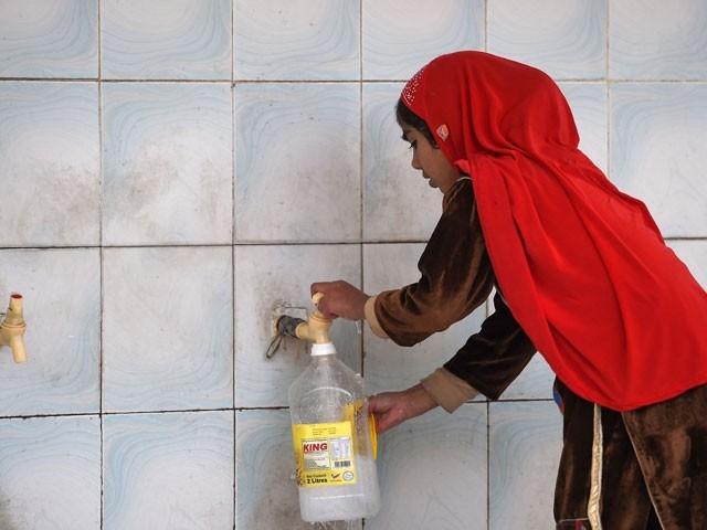 This picture taken on December 14, 2017 shows a girl filling a bottle at a water filtration plant in Islamabad. PHOTO: AFP