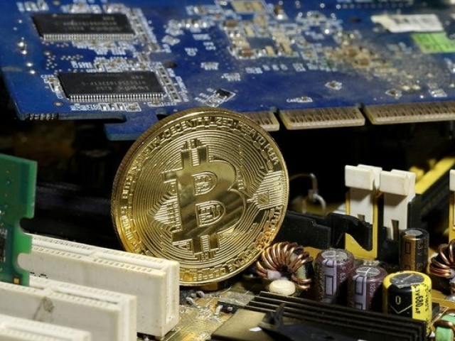 A copy of bitcoin standing on PC motherboard is seen in this illustration picture, October 26, 2017.  PHOTO: REUTERS