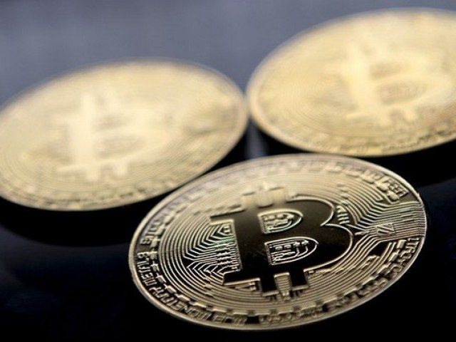 This file photo taken on November 20, 2017 shows gold plated souvenir Bitcoin coins arranged for a photograph in London.  PHOTO: AFP