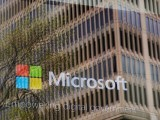 file-photo-an-advertisement-plays-behind-a-window-reflecting-a-nearby-building-at-the-microsoft-office-in-cambridge