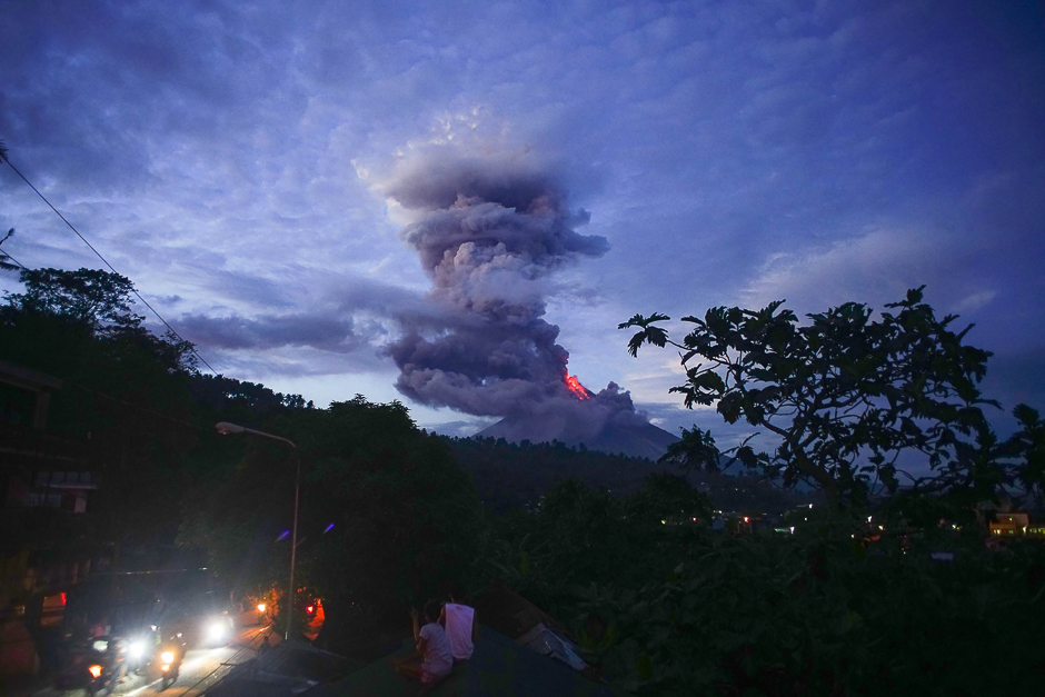 Residents watch as the Mayon volcano spews lava as it continues to erupt, in Daraga town, in Albay province, south of Manila. PHOTO: AFP