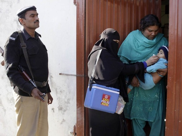 A file photo showing polio worker administering drops while a policeman stands beside her.  PHOTO: EXPRESS/FILE