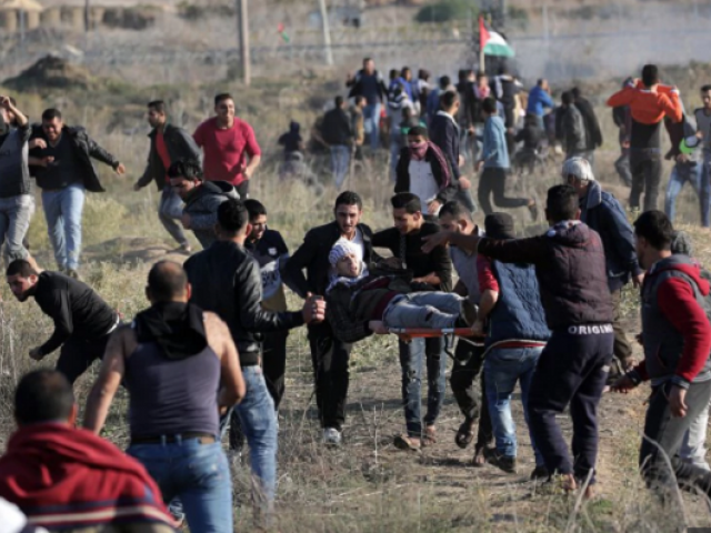 Palestinian protesters carry a wounded young during a protest against US President decision to recognize Jerusalem as the capital of Israel, during clashes along the border between Israel and east Gaza. PHOTO: AFP