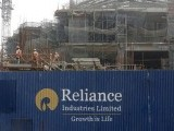 file-photo-labourers-work-behind-an-advertisement-of-reliance-industries-limited-at-a-construction-site-in-mumbai