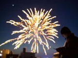 a-man-looks-at-his-phone-as-fireworks-explode-on-the-eve-of-the-chinese-lunar-new-year-or-the-spring-festival-in-lianyungang-2