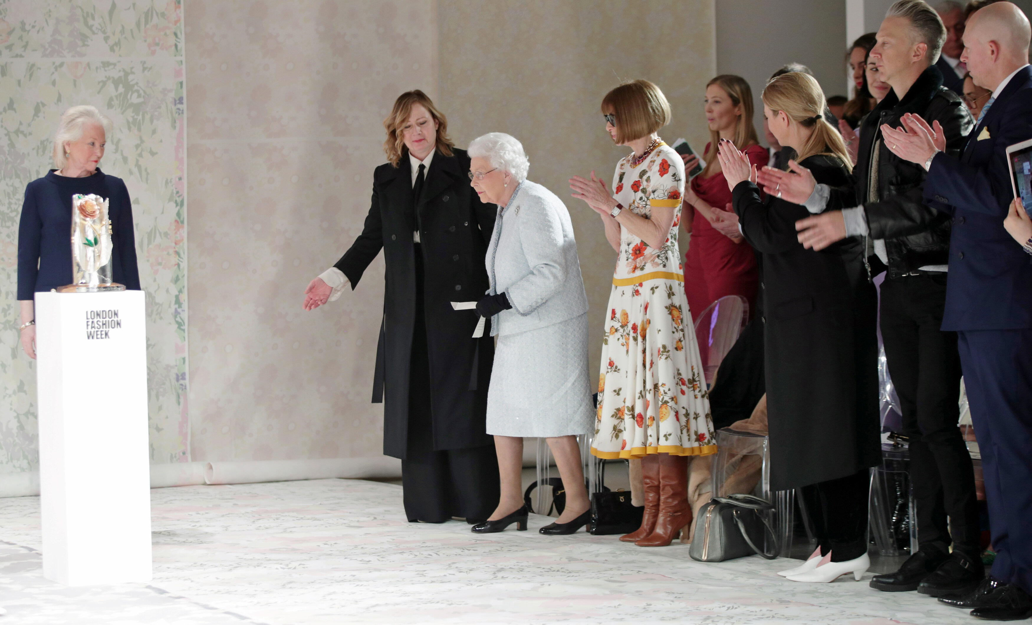 Britain's Queen Elizabeth II sits next to Vogue Editor-in-Chief Anna Wintour as they view Richard Quinn's runway show before presenting him with the inaugural Queen Elizabeth II Award for British Design as she visits London Fashion Week, in London, Britain February 20, 2018. REUTERS/Yui Mok/Pool