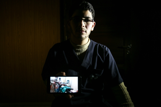 Malek Abu Jaber, a 20-year-old nurse, poses with a cell phone showing a picture of himself assisting a physician as they tend to a wounded person while he bares his own injured torso in the besieged Eastern Ghouta region on the outskirts of the capital Damascus.