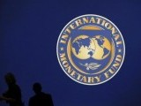 visitors-are-silhouetted-against-the-logo-of-the-international-monetary-fund-imf-in-tokyo-2-2-2-2-2