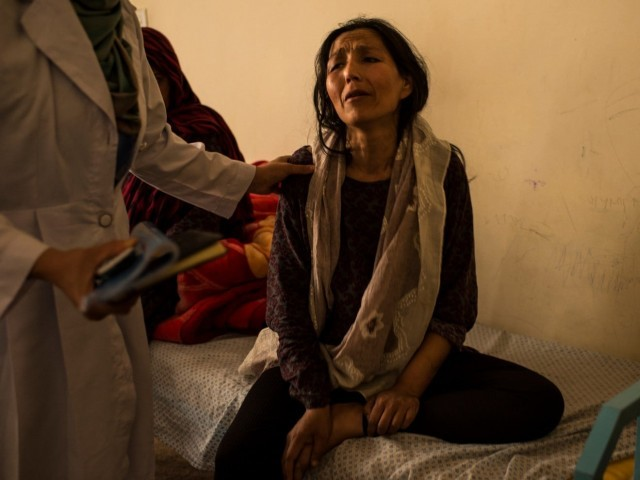 A woman recently admitted to the National Center for the Treatment of Addiction for Women and Children in Kabul is calmed by nurses and doctors after collapsing in a corridor during withdrawal from her opium addiction. PHOTO COURTESY: THE WASHINGTON POST