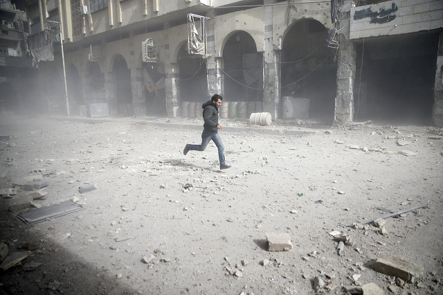 A man is seen running after an air raid in the besieged town of Douma in eastern Ghouta in Damascus, Syria, February 6, 2018 PHOTO: REUTERS