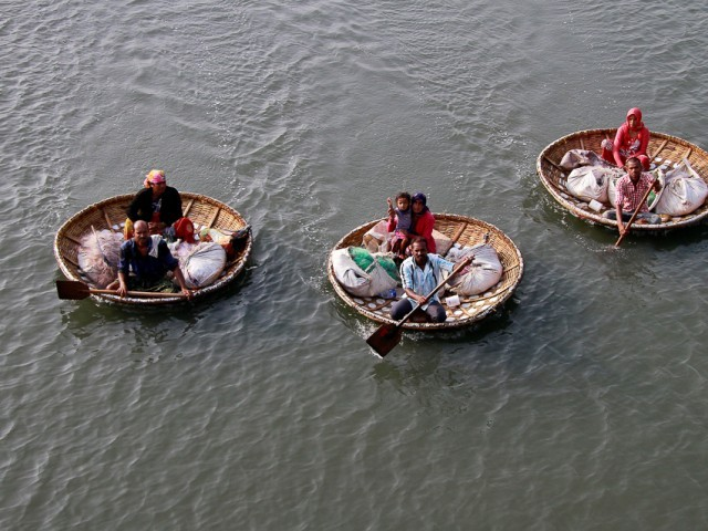 Fishermen paddle their boats as they carry their family members in the waters of Vembanad Lake in Kochi, India. PHOTO: REUTERS