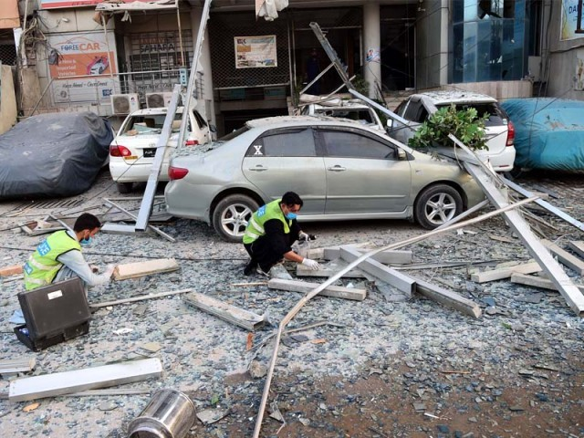 Officials collect evidence after gas explosion in a hotel in Peshawar. PHOTO: AFP