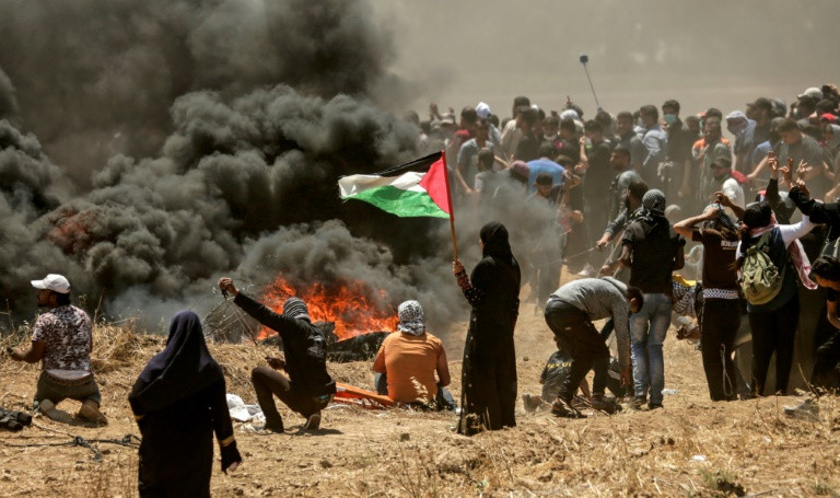 A woman holds the Palestinian flag during the Gaza border protests. PHOTO: AFP