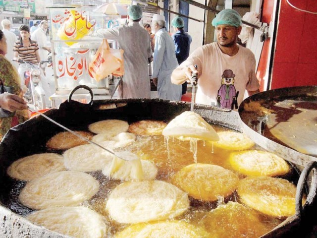 A man prepares pheni at his workplace  in Rawalpindi. PHOTO: NNI