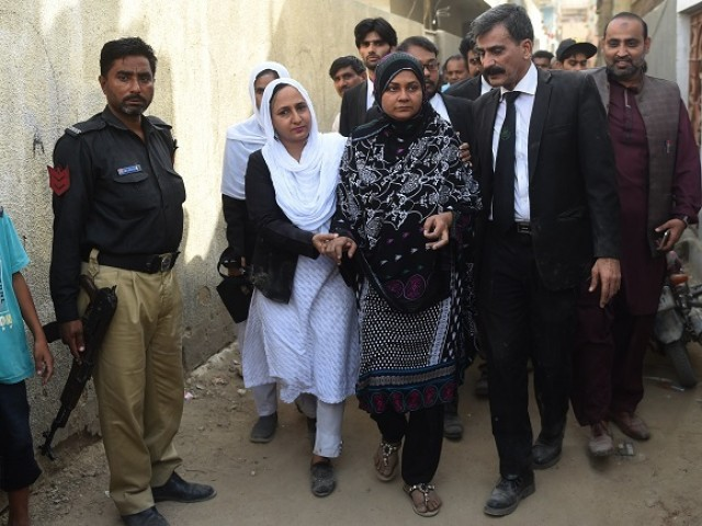 Asma Nawab (C) arrives with her lawyer Javed Chatari (2R) before entering her house after her release in Karachi. PHOTO: AFP