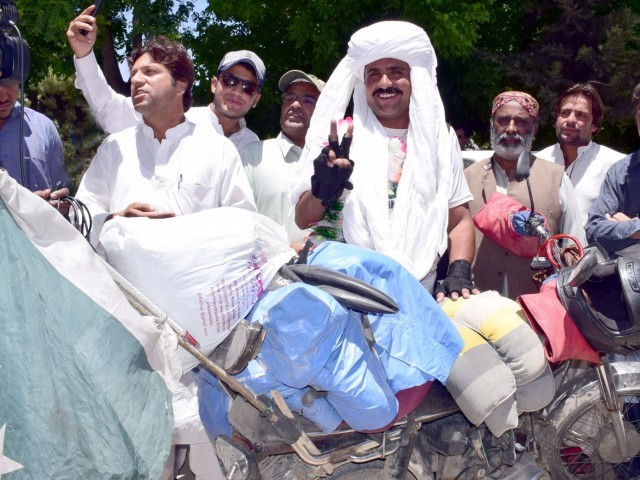 Motorcyclist Abdullah Jan Al Noor makes a victory sign on his return to Quetta. PHOTO: EXPRESS