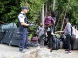 file-photo-a-family-who-identified-themselves-as-being-from-haiti-are-confronted-by-a-rcmp-officer-as-they-try-to-enter-into-canada-from-champlain-new-york