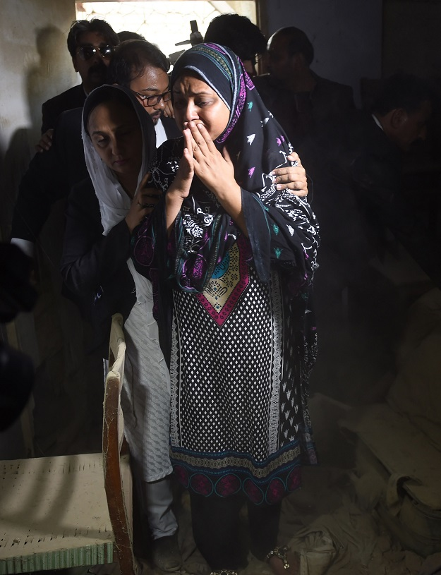 Asma Nawab (C) reacts as she enters her house after her release in Karachi. PHOTO: AFP