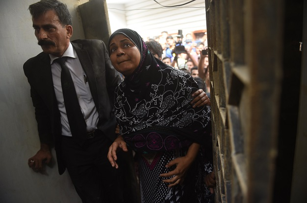 Asma Nawab (R) and her lawyer Javed Chatari enter her house after her release in Karachi. PHOTO: AFP