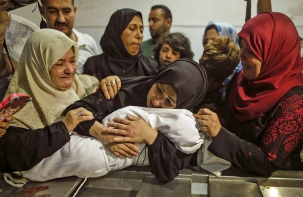 Mourners gather around as a mother holds her baby who died in the protests on  May 15, 2018. PHOTO: AFP