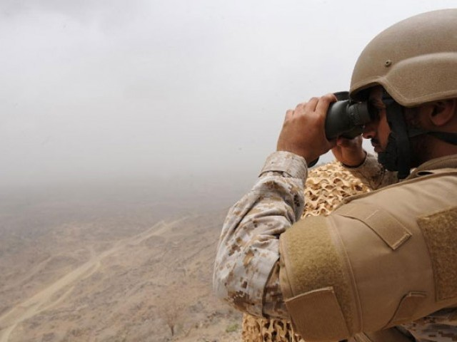 A Saudi soldier looks through binoculars from a position on the Saudi-Yemeni border. PHOTO: AFP
