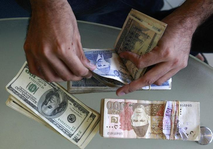 A Currency Dealer Counts Stani Rus And U S Dollars At His In Karachi Photo