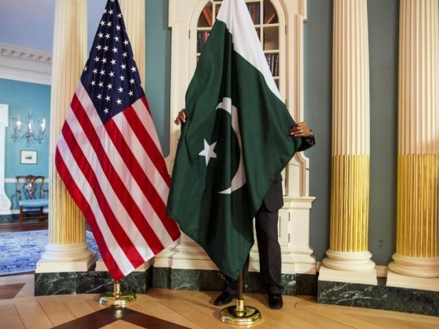 A State Department contractor adjust a Pakistan national flag before a meeting between US Secretary of State John Kerry and Pakistan's Interior Minister Chaudhry Nisar Ali Khan on the sidelines of the White House Summit on Countering Violent Extremism at the State Department in Washington February 19, 2015. PHOTO: REUTERS