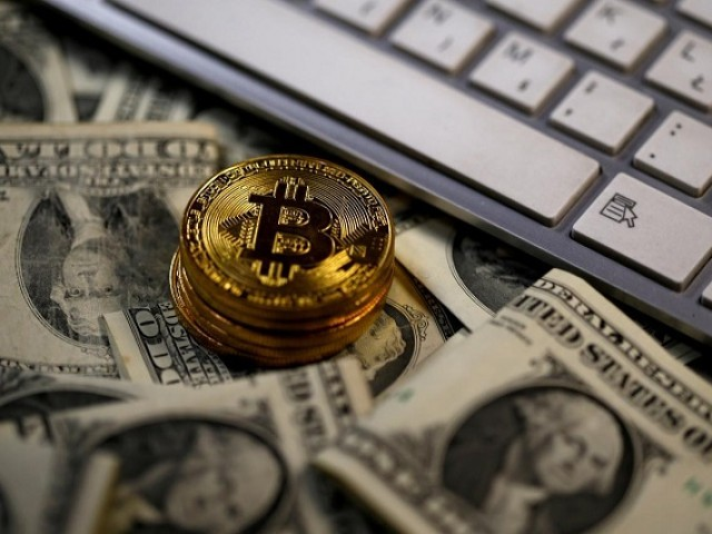 Bitcoin (virtual currency) coins placed on Dollar banknotes, next to computer keyboard, are seen in this illustration picture, November 6, 2017. PHOTO: REUTERS