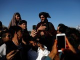People take selfies with a Taliban in Kabul, Afghanistan June 16, 2018. PHOTO: REUTERS