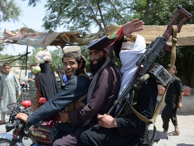 Afghan Taliban ride a motorbike as they took to the street to celebrate ceasefire on the second day of Eid on the outskirts of Jalalabad on June 16, 2018. PHOTO: AFP