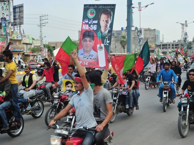 In this file photo, activists of PTI carry posters and wave flags as they drive through streets. PHOTO: AFP