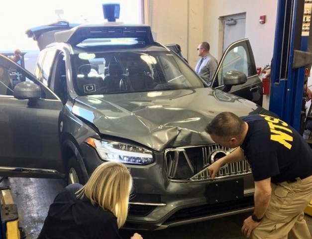 FILE PHOTO: U.S. National Transportation Safety Board (NTSB) investigators examine a self-driving Uber vehicle involved in a fatal accident in Tempe, Arizona, U.S., March 20, 2018.  A woman was struck and killed by the vehicle on March 18, 2018.  PHOTO: REUTERS