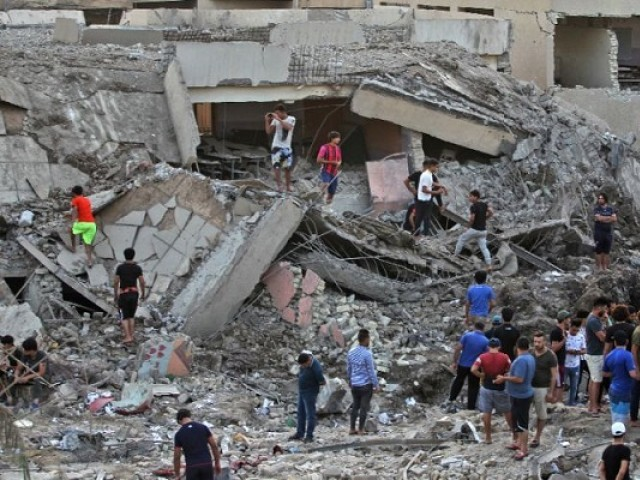 Iraqis inspect the aftermath of an explosion in an arms depot in Baghdad's Sadr City district on June 7, 2018 that killed at least 16 people. PHOTO: AFP