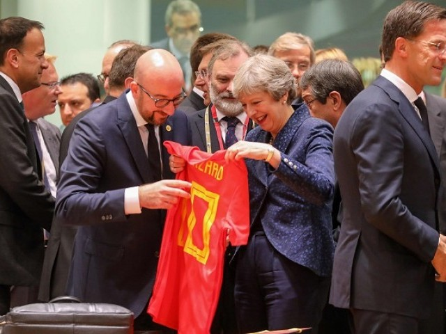 Belgium's Prime Minister Charles Michel (C-L) offers a jersey of Belgian football national team's forward Eden Hazard to Britain's Prime Minister Theresa May during an European Union leaders' summit focused on migration, Brexit and eurozone reforms on June 28, 2018. PHOTO: AFP