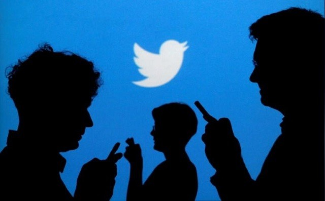 People holding mobile phones are silhouetted against a backdrop projected with the Twitter logo in this illustration picture taken in Warsaw. PHOTO: REUTERS
