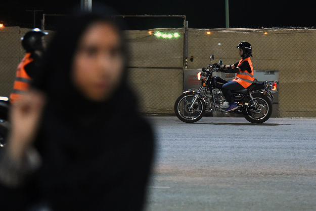 A picture taken June 3, 2018 shows Saudi Noura taking part in a training session at the Bikers Skills Institute, a motorcycle driving school, on the outskirts of Riyadh. Even a year ago, it would have been hard to imagine -- Saudi women clad in skinny jeans and Harley Davidson t-shirts, revving motorbikes at a Riyadh sports circuit. But ahead of the historic lifting of a decades-long ban on female drivers on June 24, women gather weekly at the privately owned Bikers Skills Institute, to learn how to ride bikes.   PHOTO: AFP