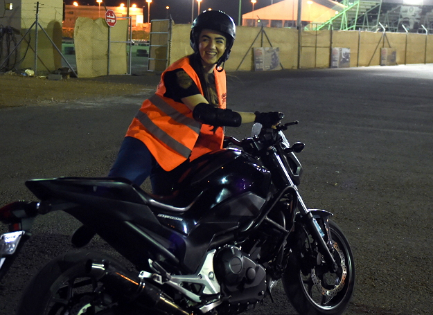 A picture taken June 3, 2018 shows Saudi-born Jordanian Leen Teenawi preparing for a training session at the Bikers Skills Institute, a motorcycle driving school, on the outskirts of Riyadh. Even a year ago, it would have been hard to imagine -- Saudi women clad in skinny jeans and Harley Davidson t-shirts, revving motorbikes at a Riyadh sports circuit. But ahead of the historic lifting of a decades-long ban on female drivers on June 24, women gather weekly at the privately owned Bikers Skills Institute, to learn how to ride bikes.   PHOTO: AFP